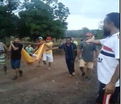 Um senhora  levada para o hospital em uma rede amarrada em um pau no ombro de homens, em São José dos Basílios MA
